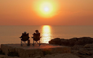 happy elderly couple watching the sunset at the sea. Image shot 2013. Exact date unknown.